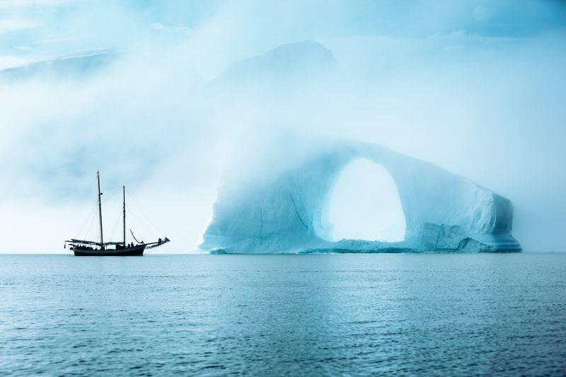 The sailing boat next to an enormous ice arch in Scoresbysund in Greenland