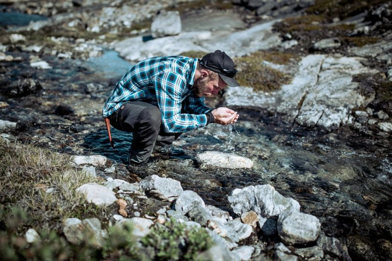 A hiker in East Greenland drinking pure, fresh water from a stream