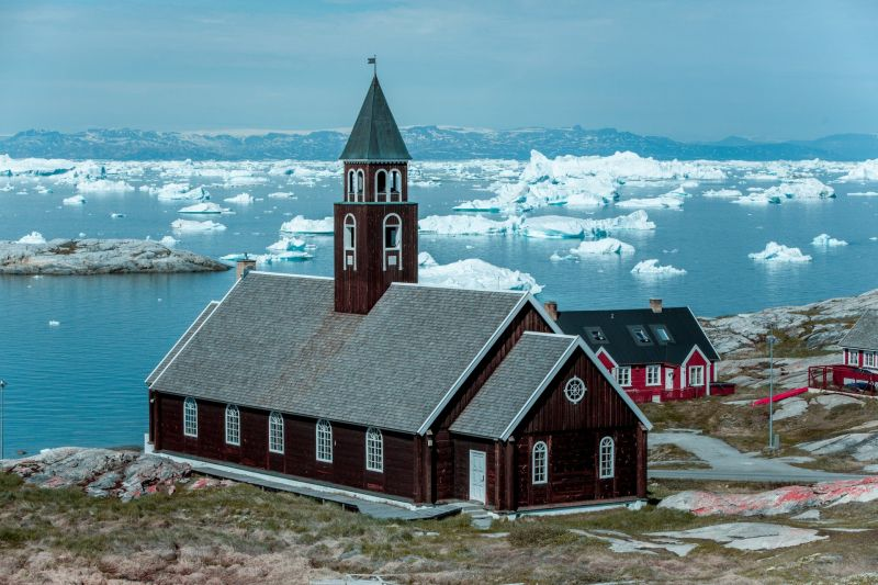 The Zion Church in Ilulissat with Disko Island in the background