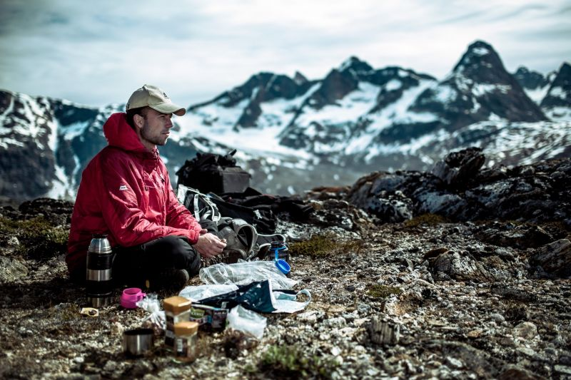 A guide making coffee for his guests on a trek near Tasiilaq in East Greenland