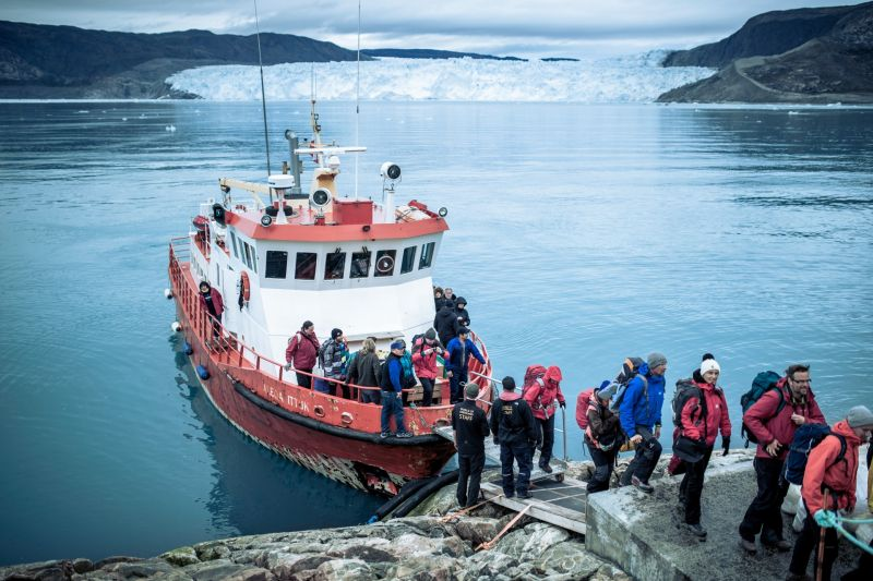 Guests arriving at Port Victor with Eqi glacier in the background