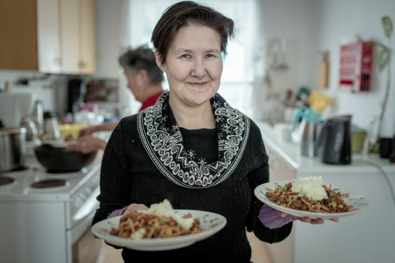 A woman serving food at a kaffemik in Oqaatsut in Greenland