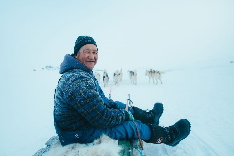 A musher and his dogs exploring the surroundings of Oqaatsut