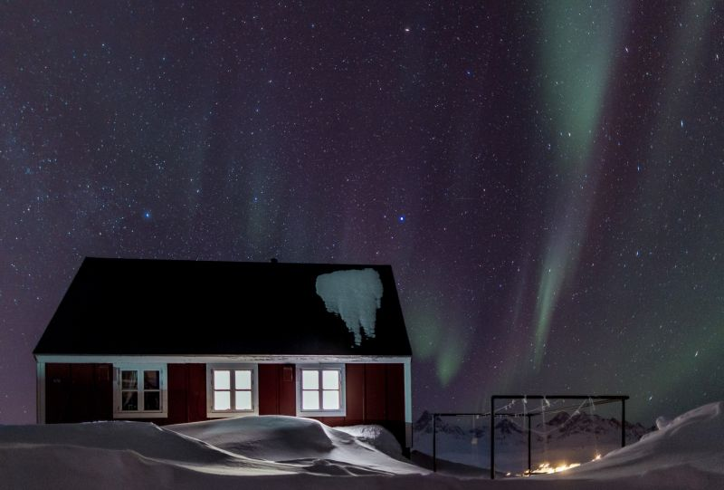 Northern lights over a house in Greenland