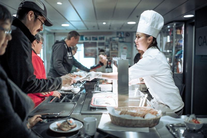 A chef serving dinner on board the Sarfaq Ittuk