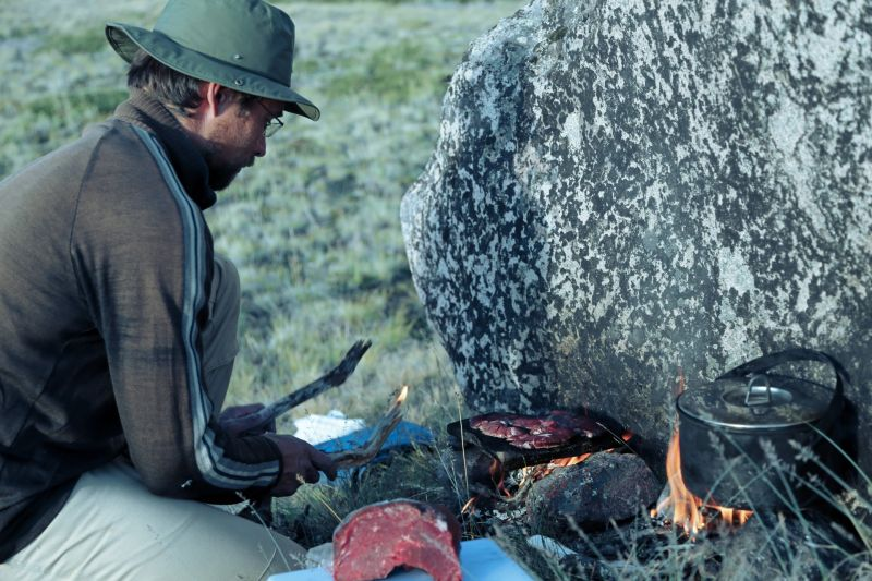 The guide preparing reindeer or musk ox meat